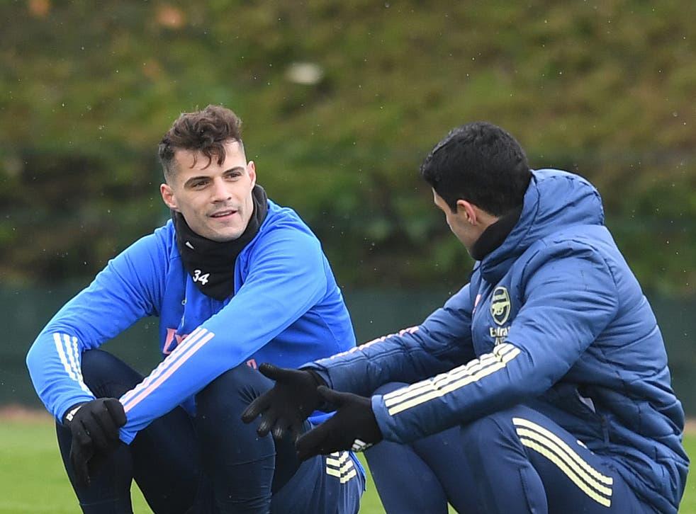 Arsenal midfielder Granit Xhaka (left) with coach Mikel Arteta
