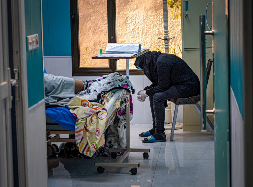 <p>A woman anxiously waits for news on her critically ill husband's condition</p>