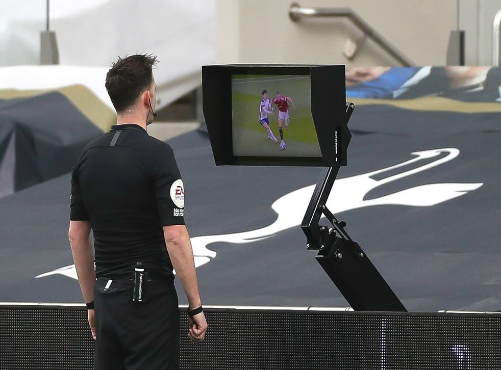 <p>Chris Kavanagh looks at the incident on his pitchside monitor</p>