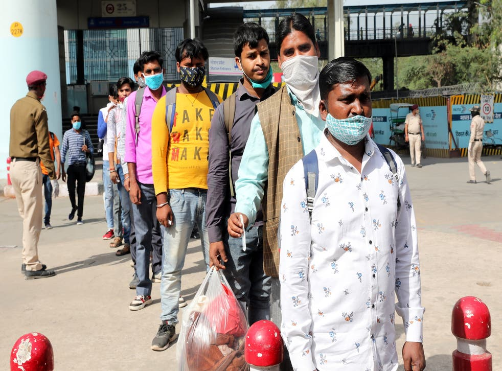 <p>People wait to undergo a Covid-19 swab test at the Anand Vihar bus station in Delhi, 8 April 2021</p>