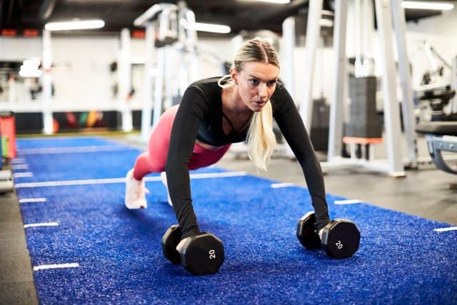 A woman doing push ups at the gym.