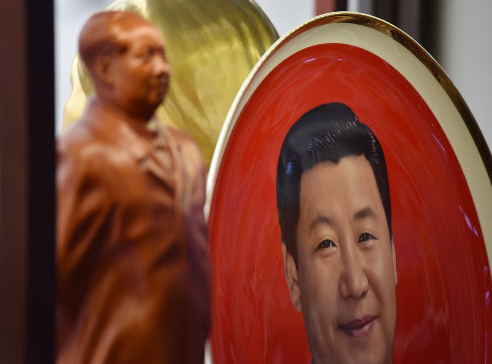 <p>A decorative plate featuring an image of Chinese President Xi Jinping is seen behind a statue of late communist leader Mao Zedong at a souvenir store next to Tiananmen Square in Beijing on 27 February, 2018</p>
