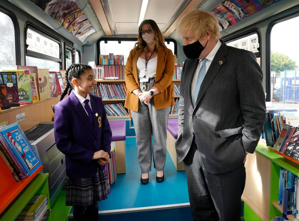 Boris Johnson speaks to a primary school student onboard a bus library during a visit to St Mary's CE Primary School last month in Stoke-on-Trent