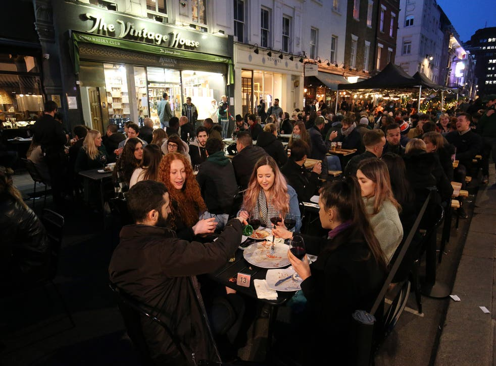 People eating and drinking outdoors in busy Soho street in London