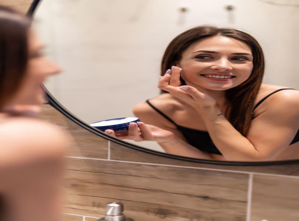 woman looking at mirror at home