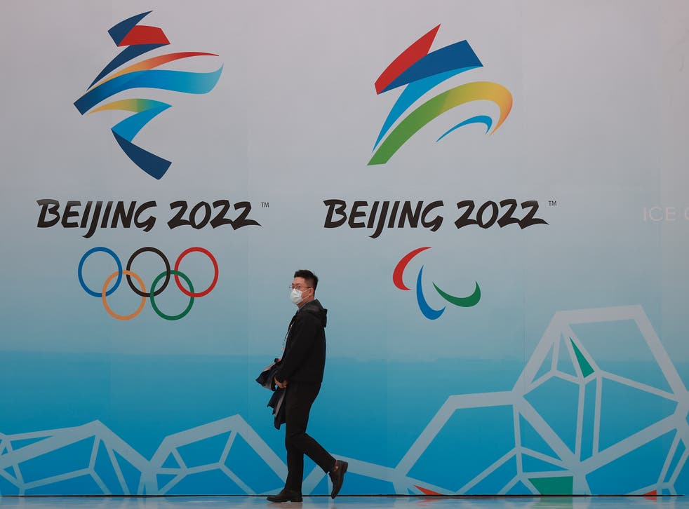 <p>A man walks in front of the logos of the 2022 Beijing Winter Olympics at National Aquatics Centre on 9 April 2021 in Beijing</p>