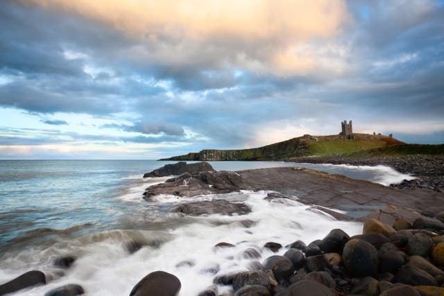 Greymare Rock and Dunstanburgh Castle at Dusk Northumberland Coast England
