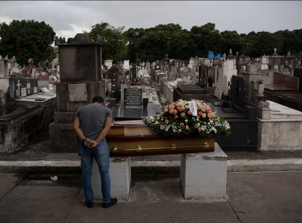 A man mourns next to the coffin containing the remains of a relative who died from complications related to COVID-19 at the Inahuma cemetery in Rio de Janeiro, Brazil