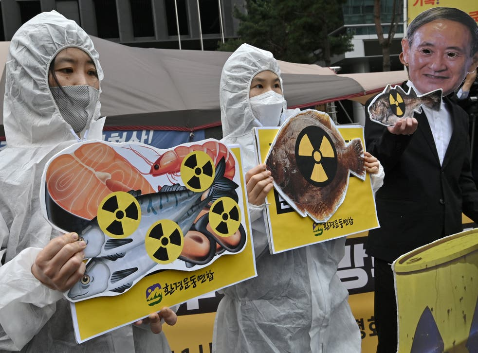 South Korean environmental activists protest outside the Japanese embassy at the decision, one wearing a mask of Japan's prime minister Yoshihide Suga