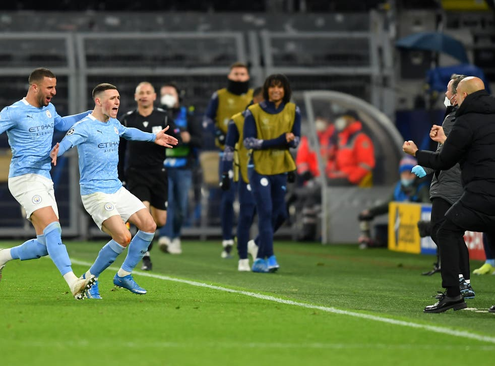 Phil Foden runs to celebrate with coach Pep Guardiola after scoring for City