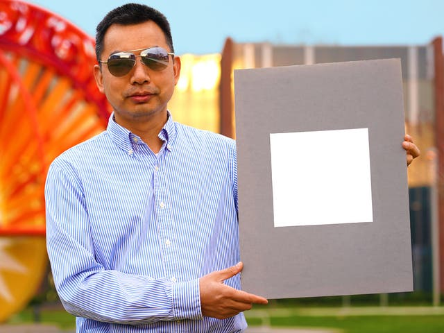 Developer Xiulin Ruan holds up a sample of the 'whitest paint'