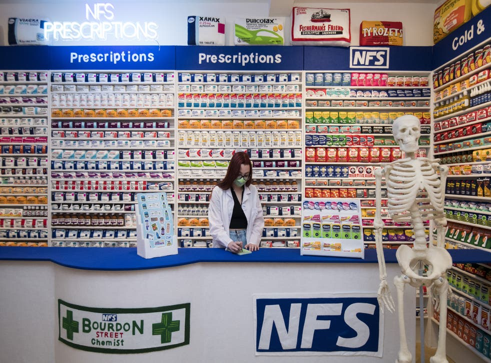 Gallery assistant Scarlett Taulbut behind the counter of artist Lucy Sparrow's NHS themed felt chemist art installation