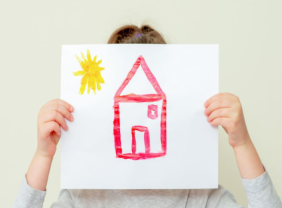 Hands of child holding picture of house covering her face on light background.