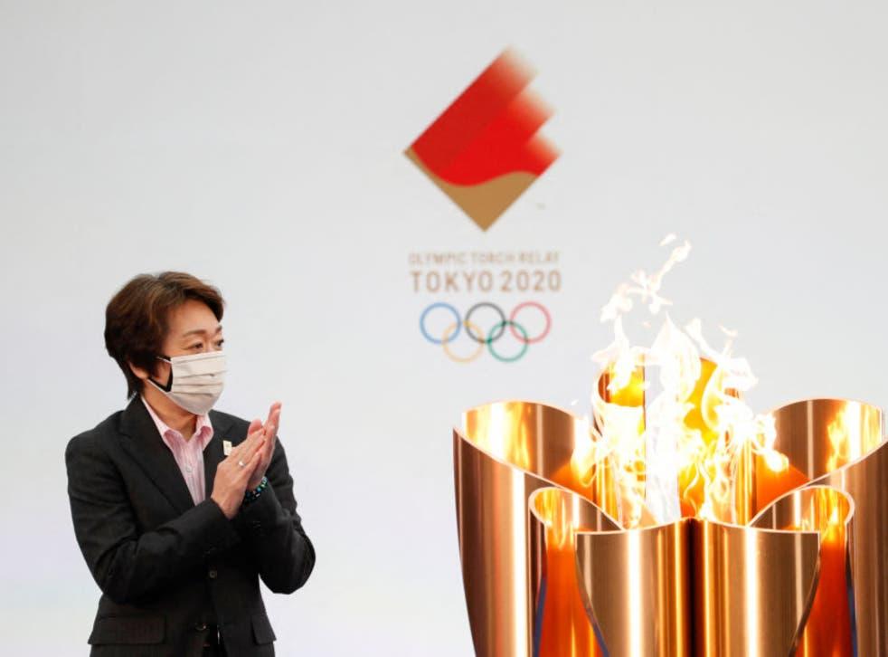 Tokyo 2020 President Seiko Hashimoto applauds next to the celebration cauldron