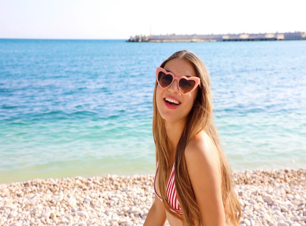 woman on beach wearing heart-shaped sunglasses