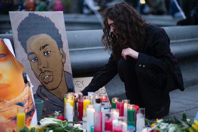 <p>A woman places a candle at a makeshift memorial in honor of Daunte Wright, who was shot dead by a police officer in Minnesota, in Washington Square, New York on April 17, 2021. Kim Potter, the police officer who shot dead Black 20-year-old Daunte Wright in a Minneapolis suburb after appearing to mistake her gun for her taser, was arrested on April 14 on manslaughter charges. </p>