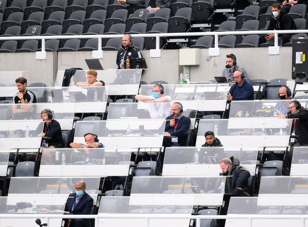 Journalists watch on from a press box