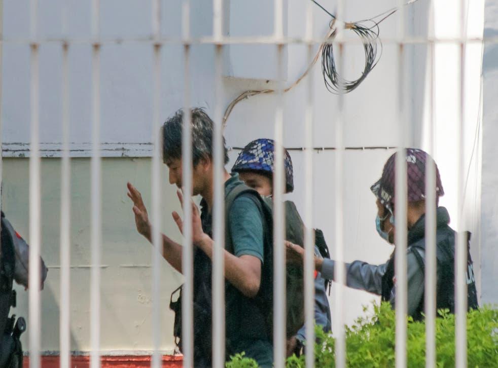 <p>Japanese journalist Yuki Kitazumi in this 26 February photo raises his hands as he is escorted by police in Yangon, Myanmar.</p>