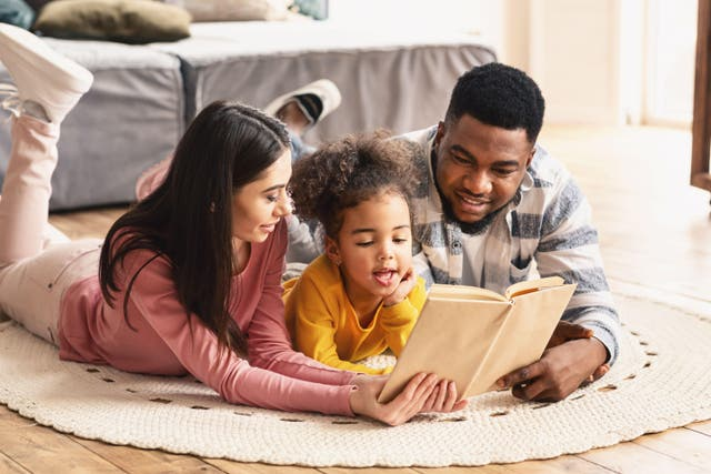 family reading book on the floor