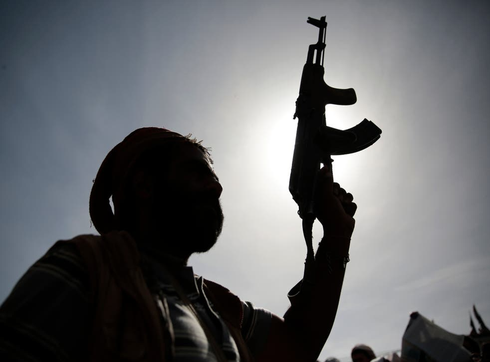 A silhouette of a Houthi supporter holds his weapon during a rally last month