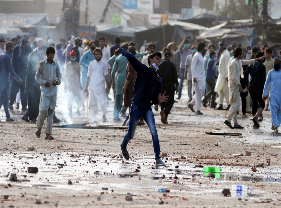 <p>An anti-French protester hurls stones towards police during a protest in Lahore, Pakistan</p>
