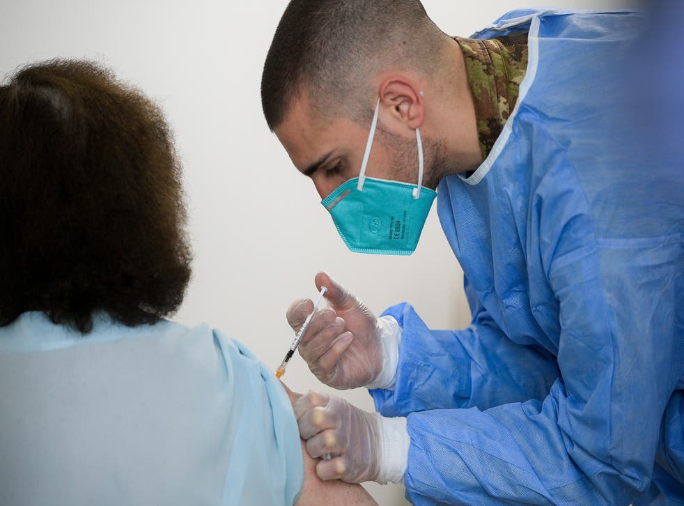 A medic administers a dose of Pfizer vaccine, in Turin, Italy