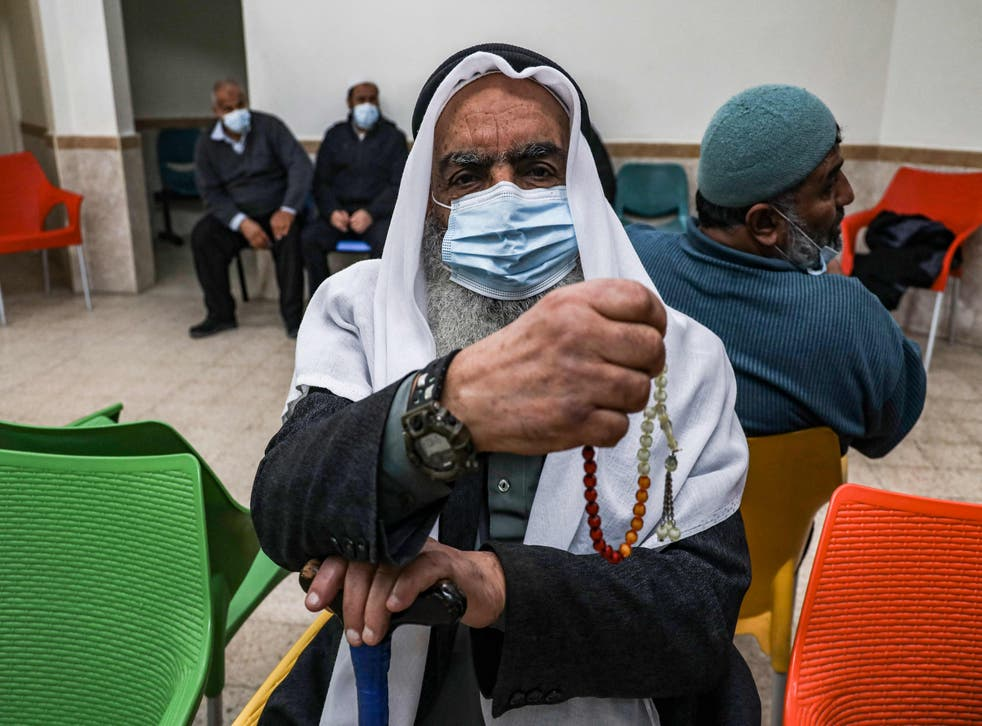 An elderly Palestinian waits to receive a dose of COVID-19 coronavirus vaccine at a clinic in Gaza City