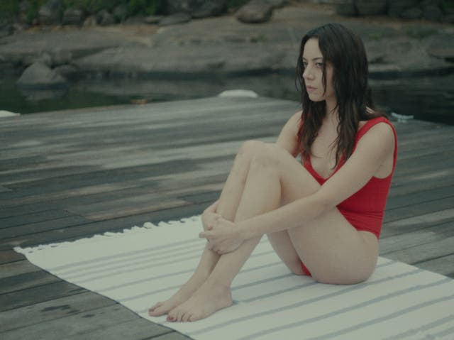 <p>'Black Bear' opens on a woman (Aubrey Plaza) in a red bathing suit. She's sat by the lake, her knees pulled up so tight that she resembles a lump of untouched clay.</p>