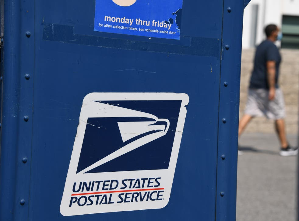 <p>A man walks past a mail box outside a post office in Los Angeles, California on 17 August 2020</p>