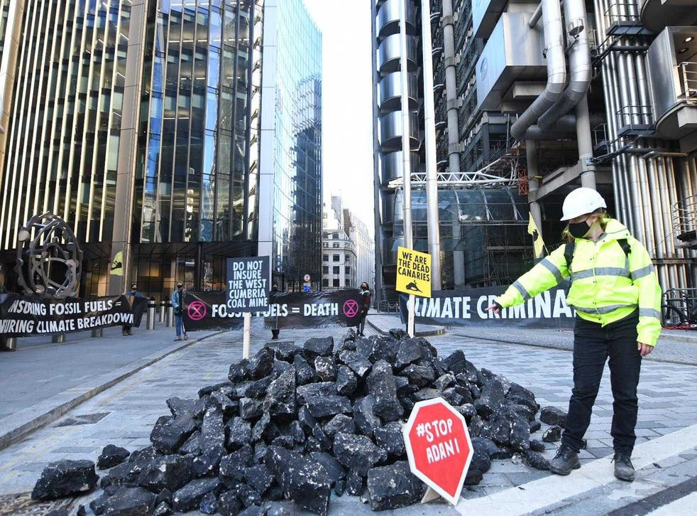 <p>An activist points to a mound of fake coal outside insurance market in central London</p>
