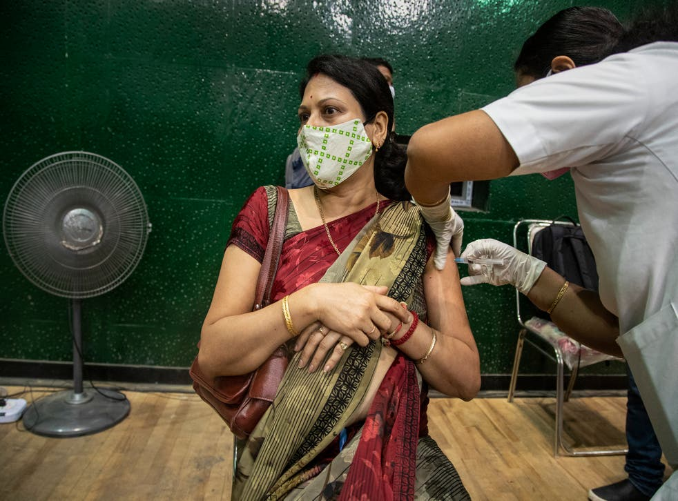 A woman receives the COVAXIN vaccine for COVID-19 at an indoor stadium in Gauhati, India