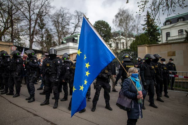 A woman holds an EU flag as people gather to protest outside the Russian Embassy on April 18 in Prague