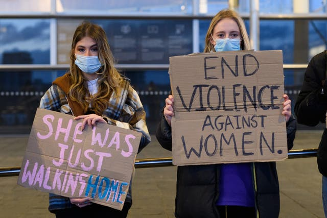 <p>Women hold placards during a vigil for Sarah Everard</p>