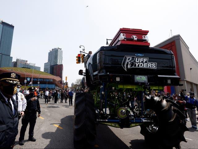 Los miembros de la policía de Nueva York se paran junto al camión monstruo que sostiene el ataúd del rapero estadounidense DMX en la avenida Flatbush, fuera del Barclays Center.