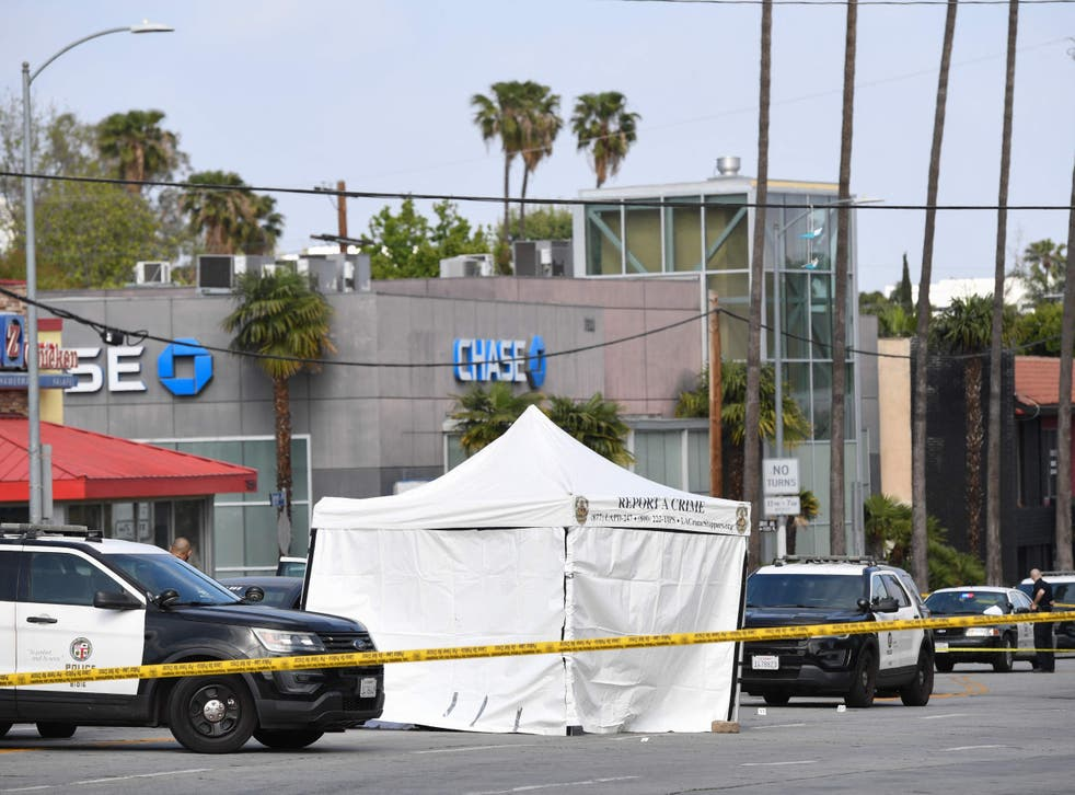 <p>LAPD police cars block the corner of Fairfax Avenue and Sunset Boulevard where a body covered in a white sheet lies under a tent in Los Angeles on 24 April, 2021</p>
