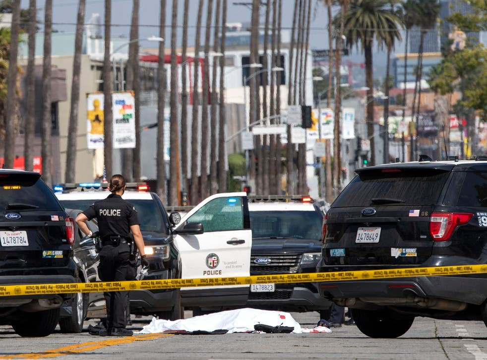 A LAPD police officer stands at the corner of Fairfax Avenue and Sunset Boulevard where a body covered in a white sheet lies on the pavement in Los Angeles on 24 April, 2021