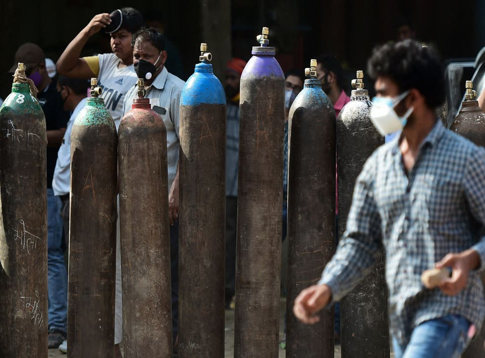 <p>Medical workers wait to refill oxygen cylinders in Allahabad</p>