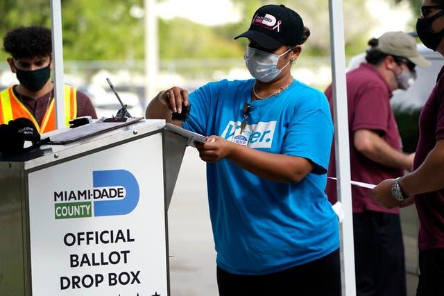 Un trabajador electoral sella una boleta de voto por correo entregada por un votante antes de colocarla en una urna oficial de entrega de boletas.