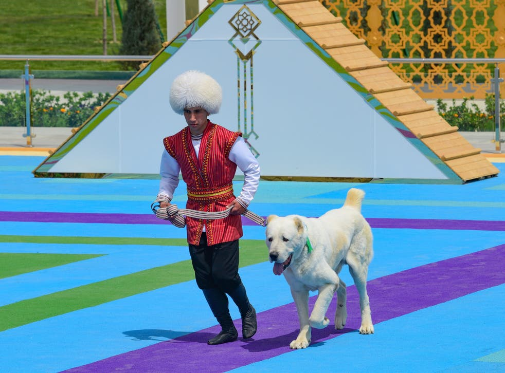 A man dressed in a national costume runs with his border guard shepherd dog Alabay during Dog Day celebration in Ashgabat, Turkmenistan