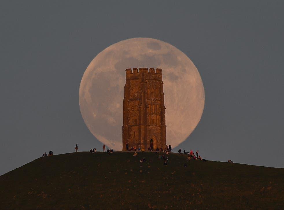 Hëna e plotë ngrihet pas Glastonbury Tor në 26 Prill 2021 në Glastonbury, Angli
