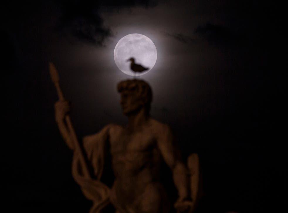Një super hënë ngrihet përmes reve prapa një statuje të Vittoriano në Romë, Itali