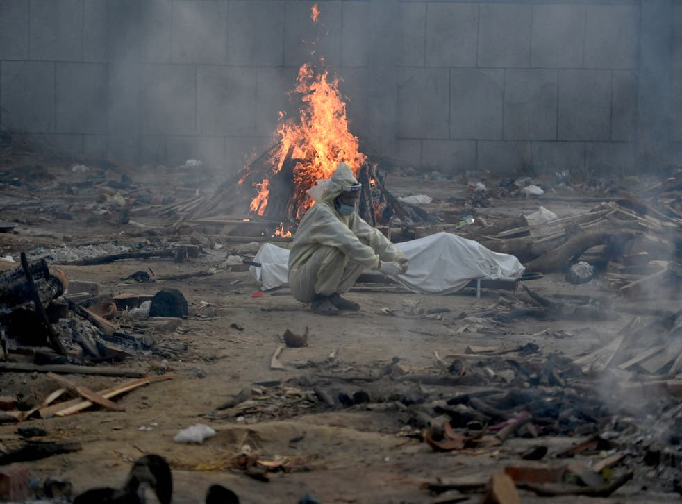 <p>A man sits next to the body of a victim who died of the Covid-19 coronavirus besides the burning pyre of another victim at a cremation ground in New Delhi on April 26, 2021.</p>
