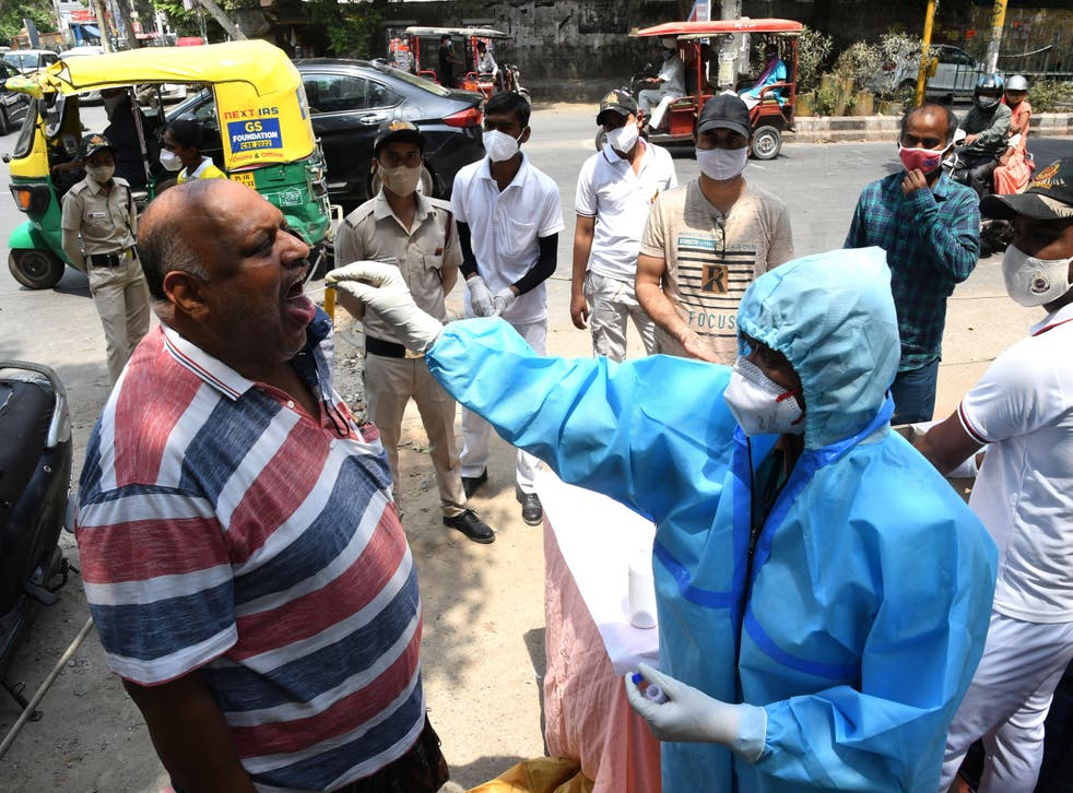 <p>A health worker takes a swab sample to test for Covid-19 at a roadside testing centre in Delhi</p>