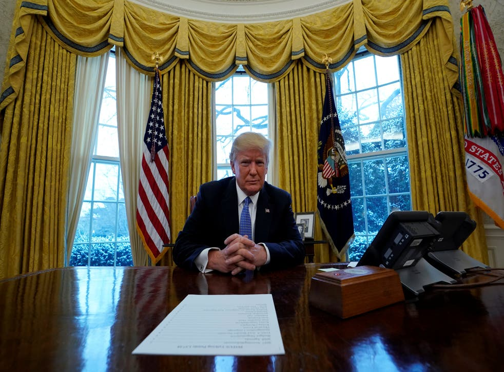 Donald Trump sits at the Resolute Desk