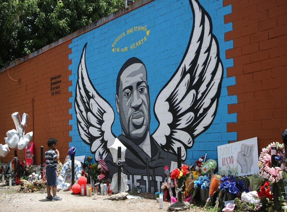 <p>A child views a mural dedicated to George Floyd, across the street from the Cuney Homes housing project in Houston's Third Ward, where Floyd grew up and later mentored young men, on June 10, 2020 in Houston, Texas. </p>