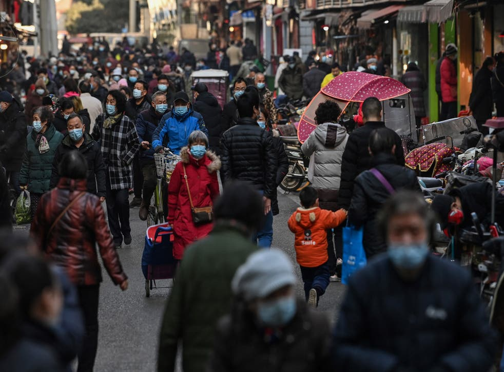 <p>People walk along a street near a market in Wuhan, China's central Hubei province on 19 January, 2021.</p>