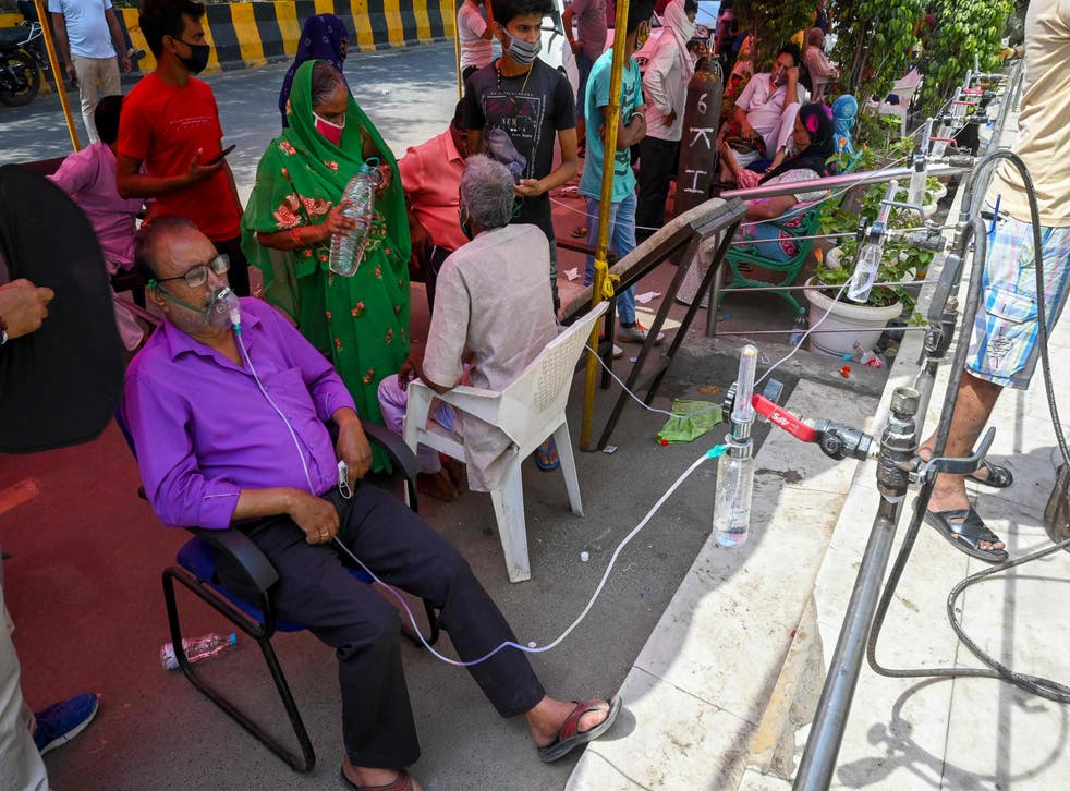<p>Covid-19 coronavirus patients breathe with the help of oxygen provided by a Gurdwara, a place of worship for Sikhs, under a tent installed along the roadside in Ghaziabad, Uttar Pradesh</p>