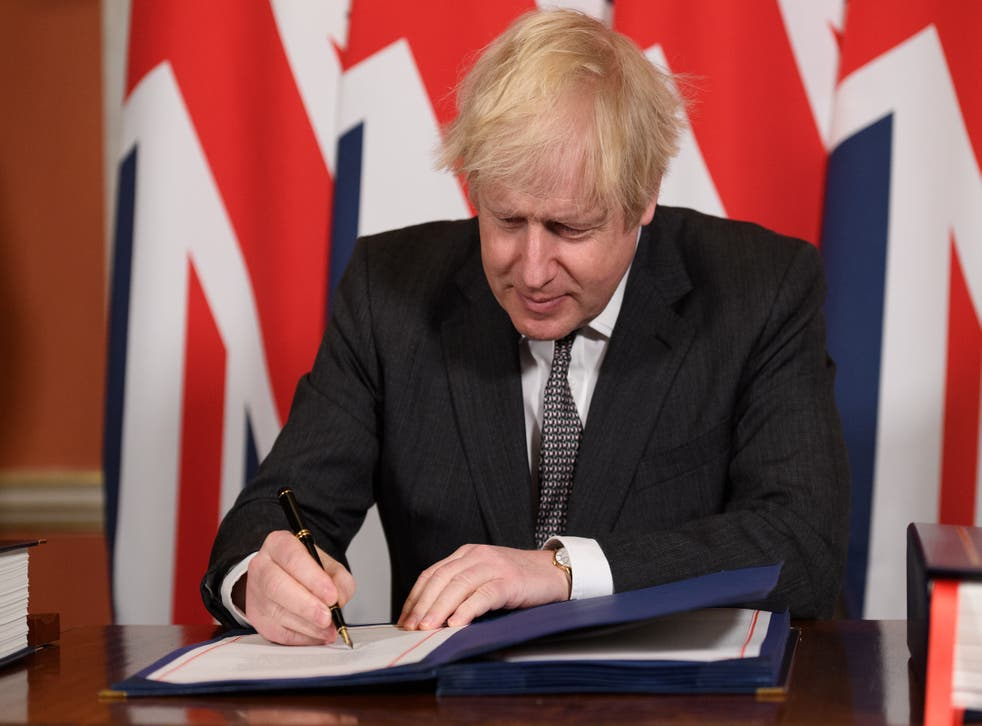 Boris Johnson signs a page of the Brexit trade deal with the EU in number 10 Downing Street on December 30, 2020