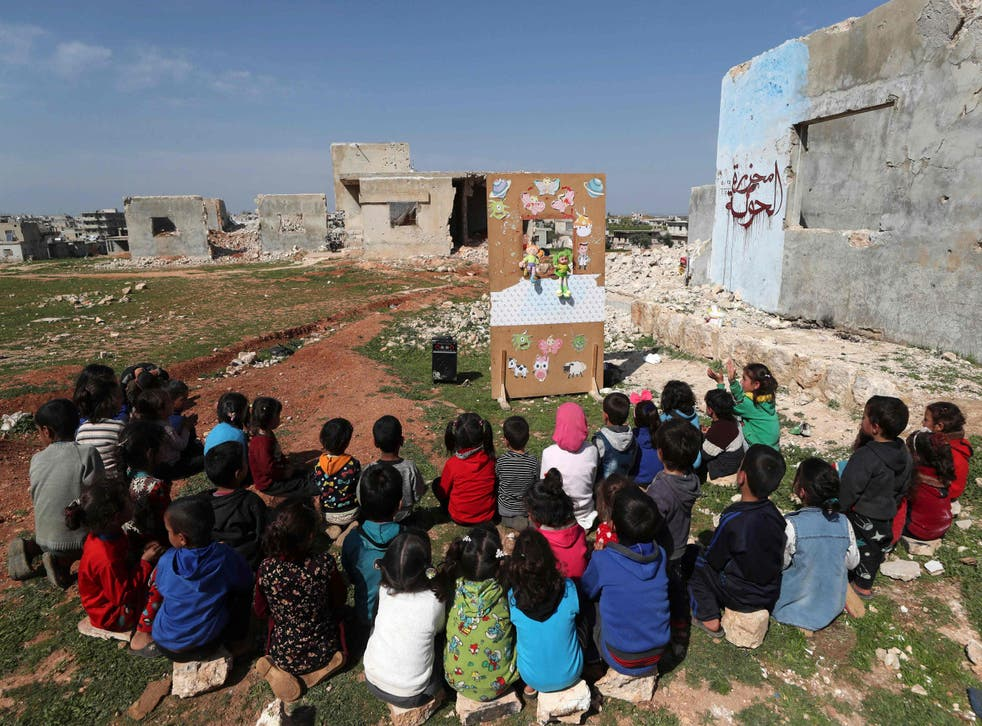 Syrian children watching a makeshift puppet show in the country's northwestern Idlib province last month