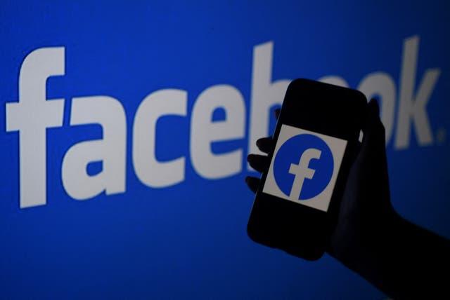 La pantalla de un teléfono inteligente muestra el logotipo de Facebook en el fondo de un sitio web de Facebook